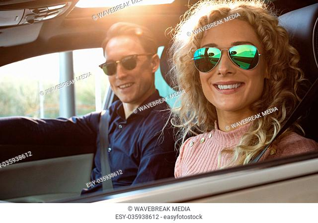 Portrait of smiling couple sitting in car
