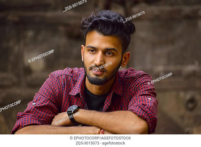 Young man with checked shirt looking at camera, Pune, Maharashtra