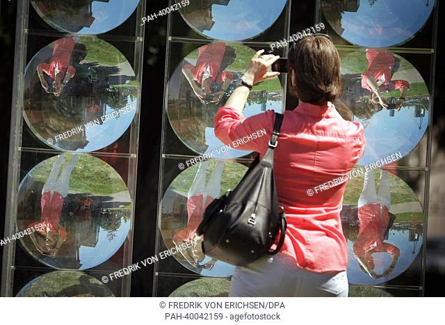 "A woman takes pictures of the installatioon """"Integration Sphaerische Hohlspiegelwand"""" by Adolf Luther in the exhibition """"Architecture as Light and..."