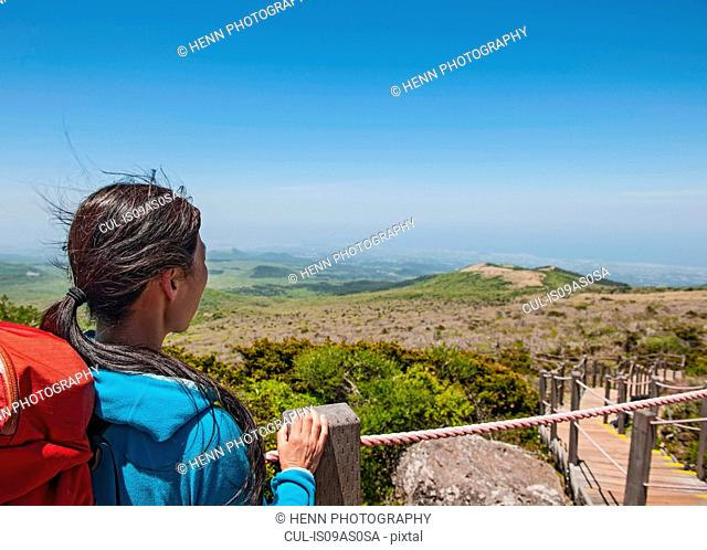 Hiker enjoying the view on the way to Hallasan, the highest mountain in Korea, Jeju Island, South Korea