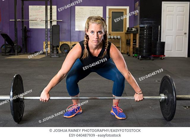 Fit female lifting weights at a crossfit gym that focuses on health and fitness for the female athlete