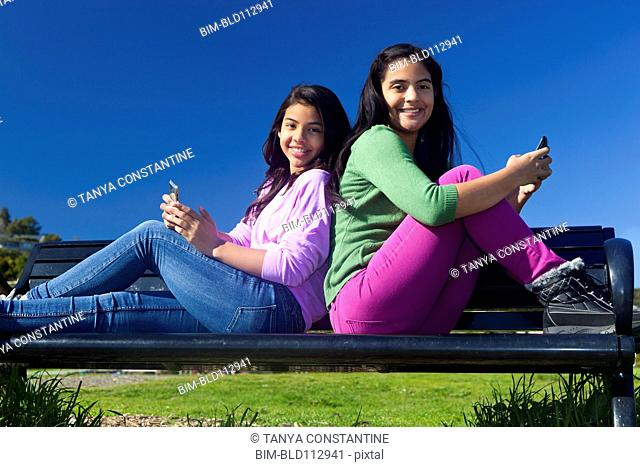 Hispanic teenage girls sitting on park bench