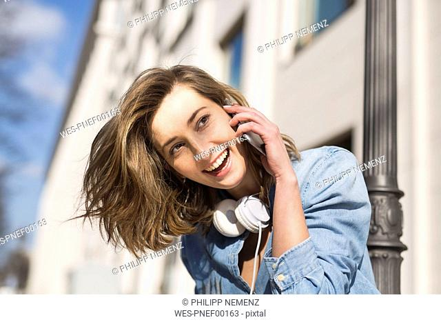 Portrait of laughing woman with headphones on the phone