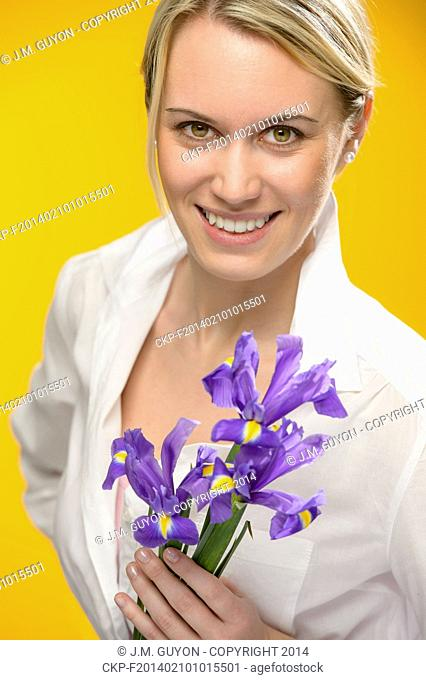 Smiling woman hold one blue iris spring flower smiling