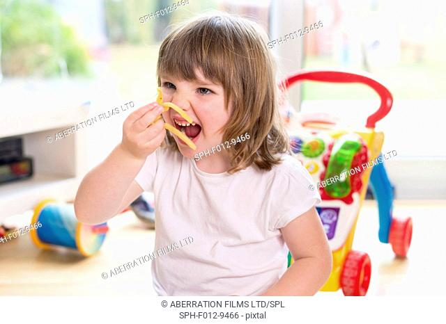 MODEL RELEASED. Young girl eating french fries