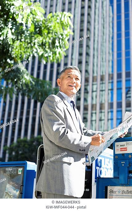 Businessman holding newspaper
