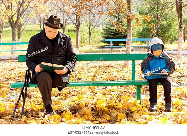 Elderly handicapped man on crutches and a small boy sitting on a park bench in the autumn sun each engrossed in reading a book and tablet-pc