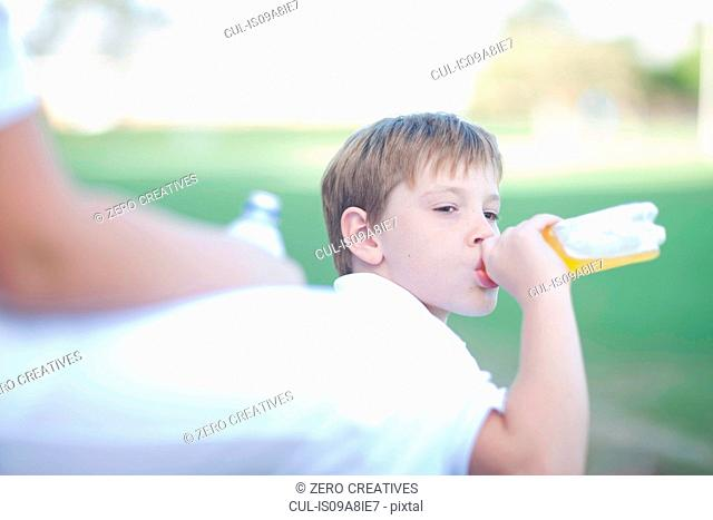 Boy drinking soft drink during game of cricket