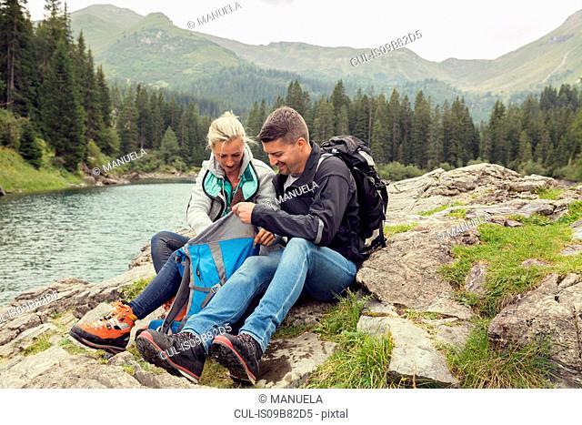 Couple hiking, sitting by lake looking at smartphone, Tirol, Steiermark, Austria, Europe