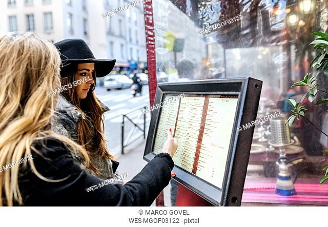 France, Paris, two female tourists browsing the menu of a restaurant