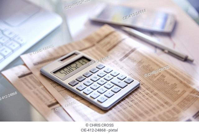 Calculator,close up,newspaper and pen on desk