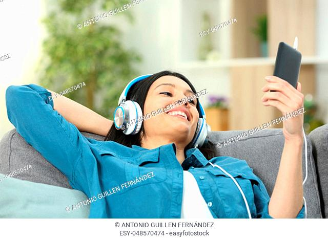 Happy woman listening to music from smart phone sitting on a couch in the living room at home