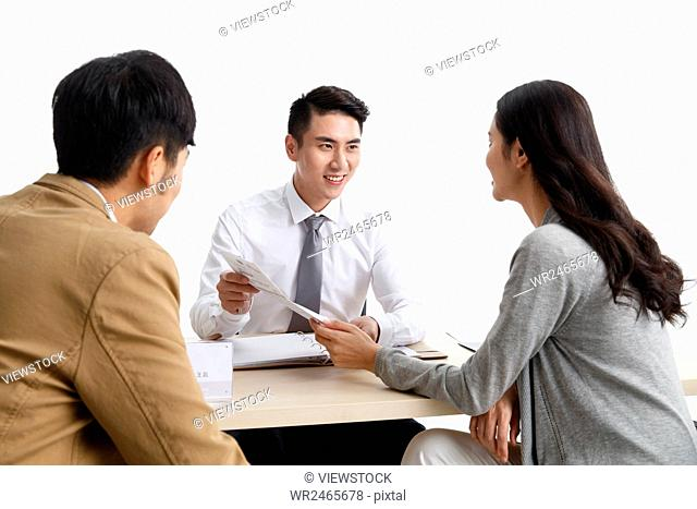 Young couple with car dealer in showroom