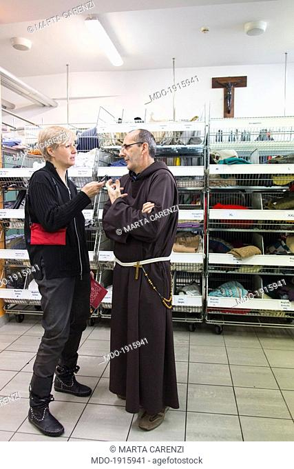 A woman and a friar inside a store. Milan (italy), 28th March 2014