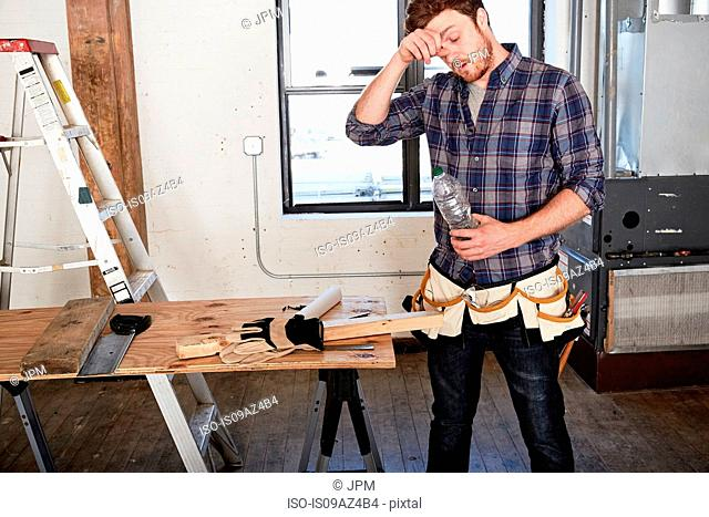 Carpenter in workshop holding water bottle wiping brow