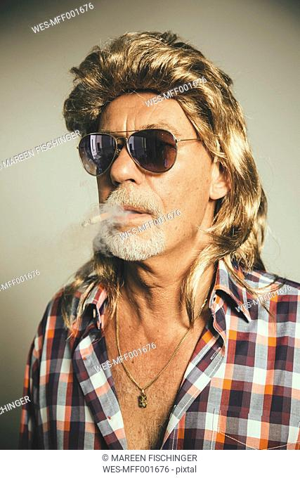 Portrait of smoking man wearing sunglasses and blond wig