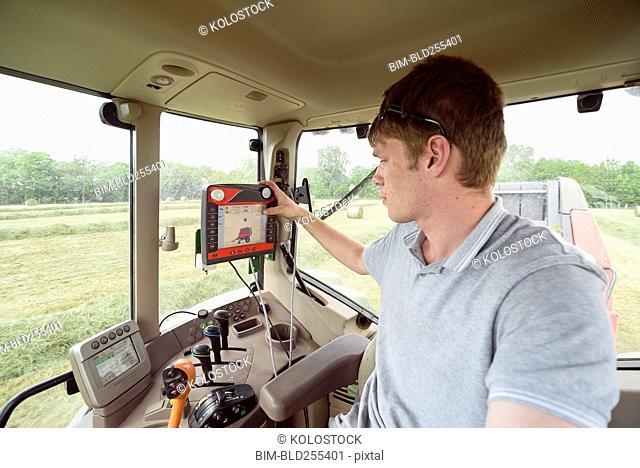 Caucasian man setting control panel in tractor on farm