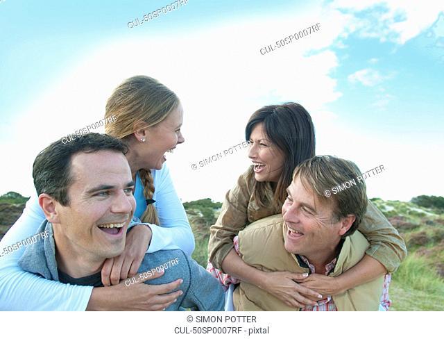 Smiling men carrying women outdoors