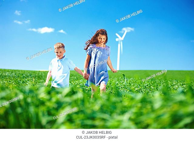 Wind turbine, boy and girl on field