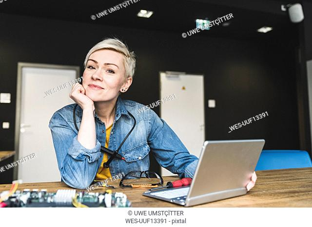 Portrait of smiling woman with laptop and computer equipment