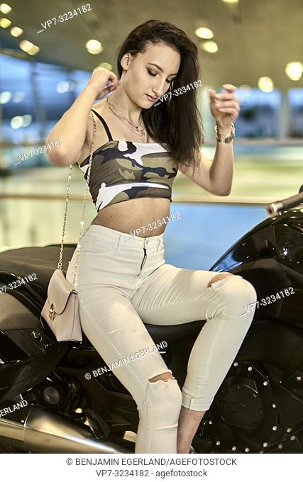 fashionable woman sitting on motorbike