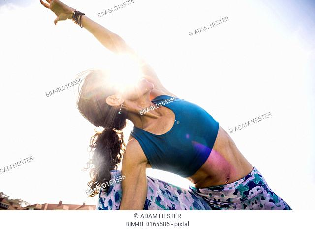 Low angle view of Hispanic woman practicing yoga outdoors