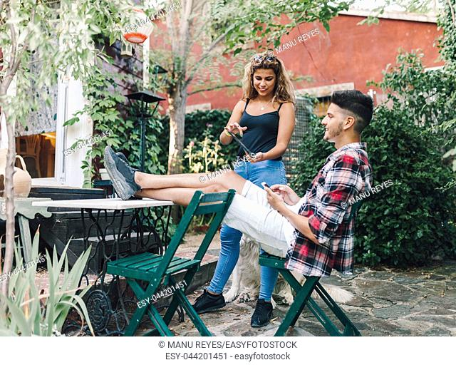 Smiling young couple sitting in the garden chairs near their wooden house with their smart phone