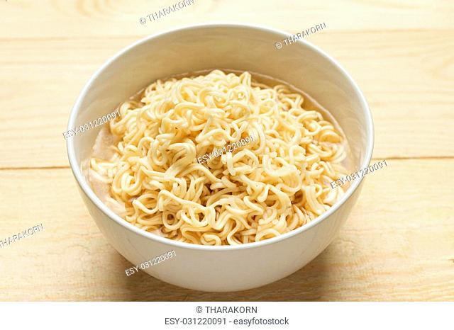 Instant noodles in white dish on wood background