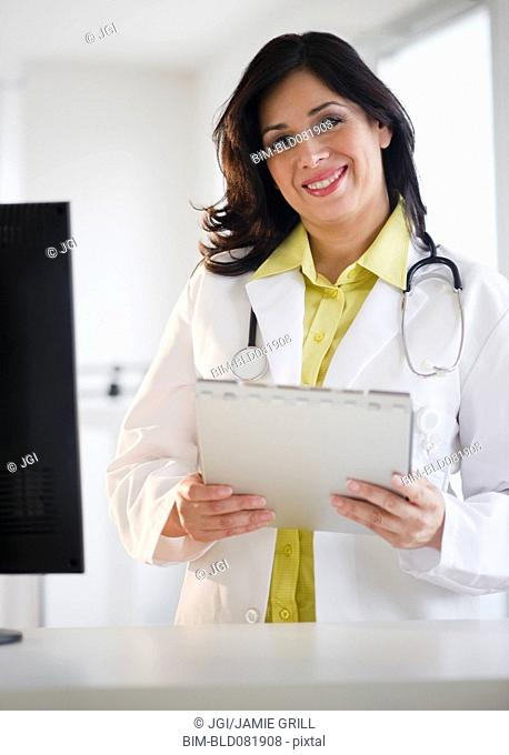 Smiling Hispanic doctor holding medical record
