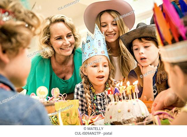 Three generation family at kids birthday party watching girl blowing out candles