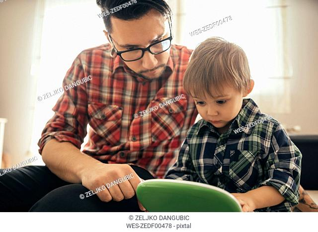 Father and son with toy laptop