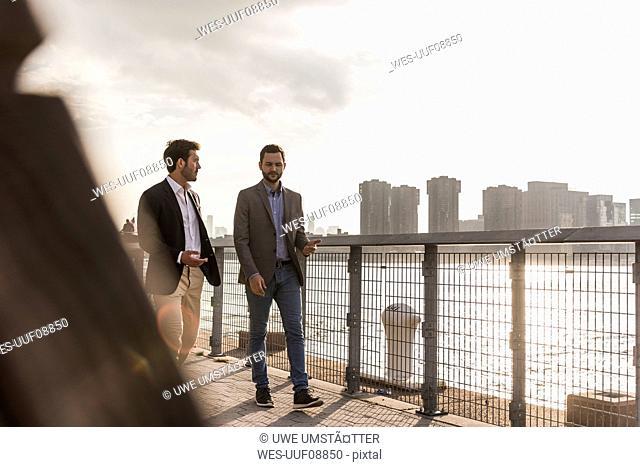USA, New York City, two businessmen walking along East River
