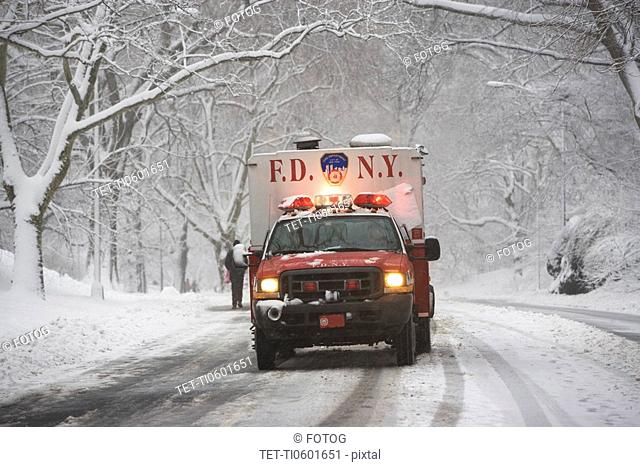 New York City fire department vehicle driving on snowy road