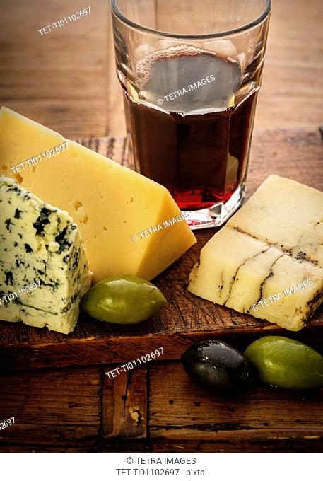 Assorted cheeses with olives and red wine