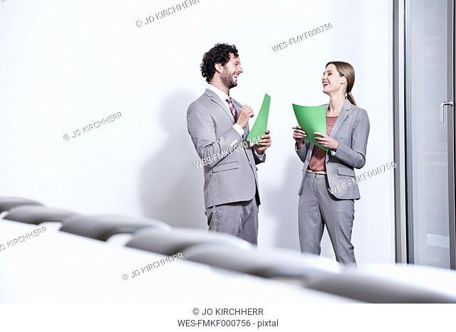 Germany, North Rhine Westphalia, Cologne, Businesscouple holding files, smiling