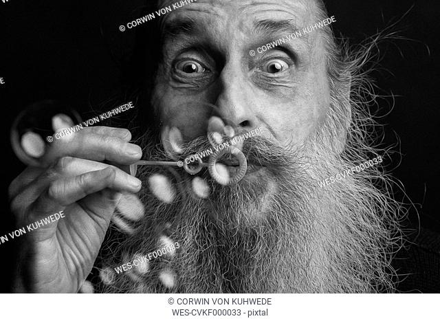 Portrait of an old man with beard blowing soap bubbles