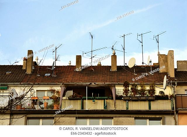 Row of apartments, showing roof with TV antennae and satellite dishes. Photo taken in Germany
