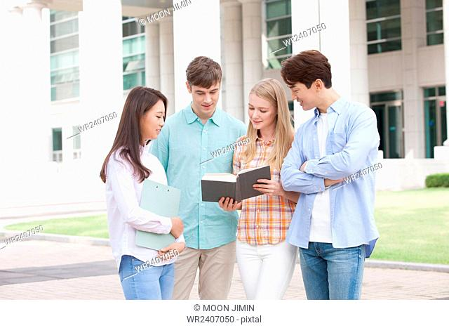 International students and domestic students in college looking at a book together on campus outside