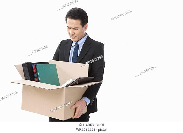 Middle aged businessman carrying files in a box frowning his face