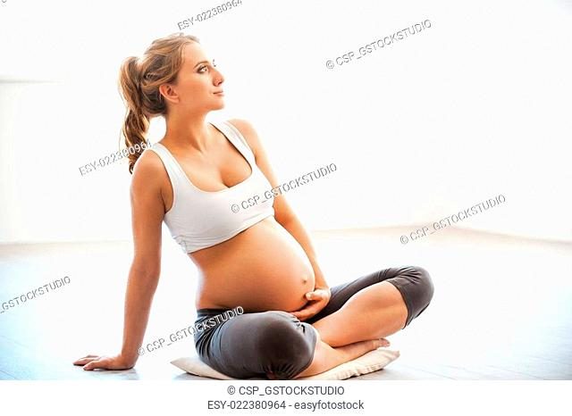 Relaxation for both of them. Portrait of pregnant young woman touching her belly while sitting in lotus position
