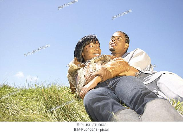 Couple laying on grass together
