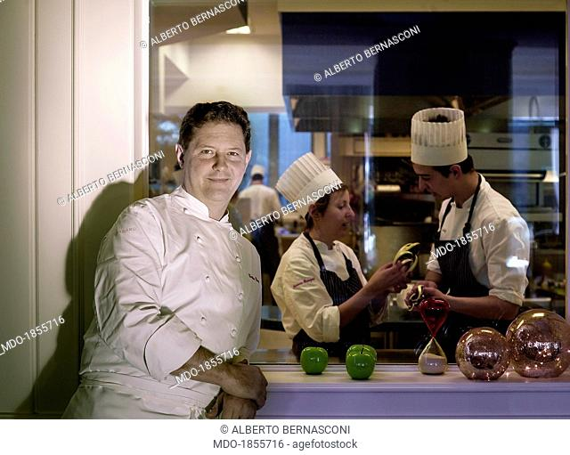 Italian chef Enrico Cerea known as Chicco leaning on the kitchen window in front of two cooks chatting about something. Photocall shooted at his restaurant...