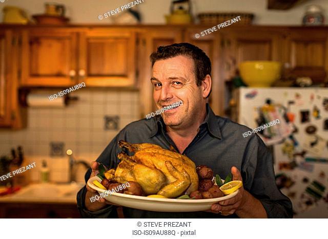 Portrait of mature man holding roast chicken dinner in kitchen