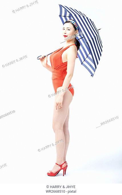 Side view of young woman wearing orange swimsuit and an umbrella with stripes