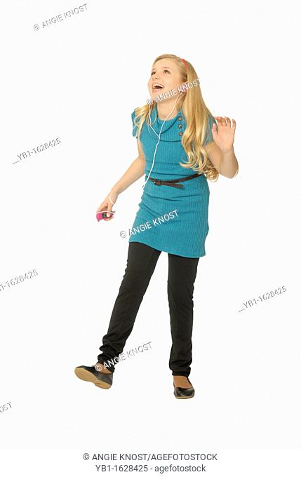 Ten year old girl wearing earbuds, listening to mp3 player and dancing