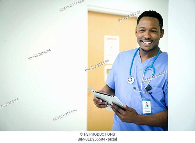 Portrait of smiling black nurse holding digital tablet