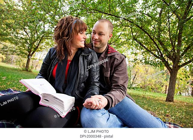 couple reading bible together in the park, edmonton alberta canada