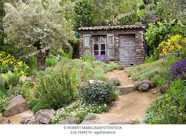 Mediterranean styled garden with flowerbeds and old cottage, Chelsea Flower Show 2012 London