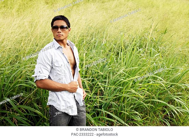 A stylish man standing in a grassy field; Hawaii, United States of America