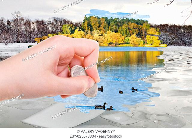 weather concept - hand deletes ice blocks in winter river by rubber eraser from image and autumn natural landscape are appearing